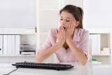 Junge Frau sitzt gähnend und schläfrig im Büro