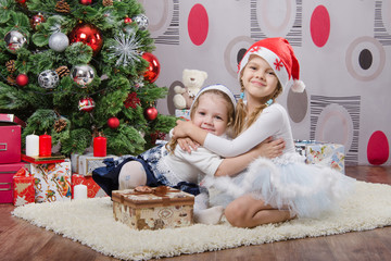 Sisters with gifts at Christmas tree