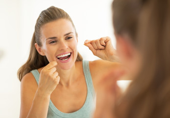 Portrait of young woman using dental floss in bathroom