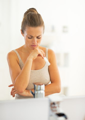 Concerned young woman with pregnancy test in bathroom