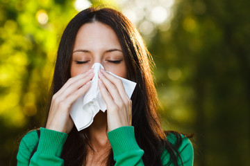 Woman blowing nose in nature