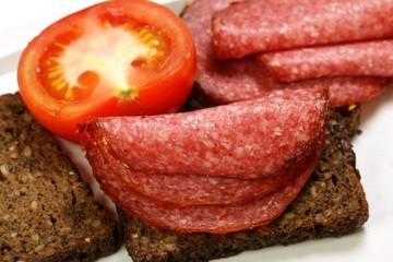 salami, tomato, grainy bread on a white background