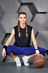 Beautiful girl sitting with a basketball