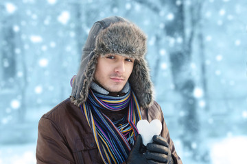 Young man in an ear flap hat holding a heart shaped snowball