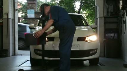 Car Repair Mechanic Adjusting Headlights
