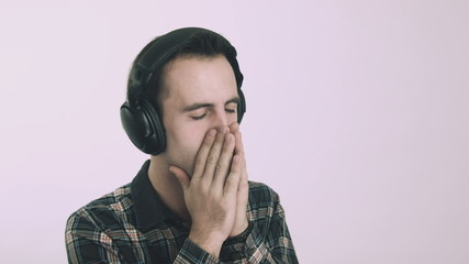 Young sad man listening to music on headphones