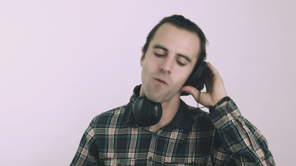 Young male Dj listening to music on headphones