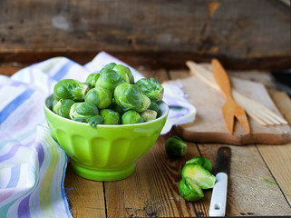 Brussels sprouts in a bowl on a wooden background