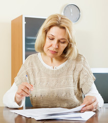 serious mature woman filling in financial documents