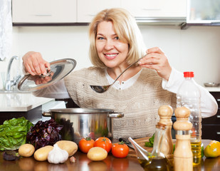 mature woman with ladle cooking soup in pan at  kitchen