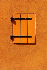 Orange colored building with shutter.