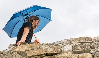Girl holdingan umbrella smiling from a wall