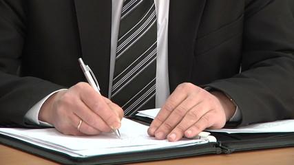 businessman writes document