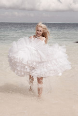 young beautiful woman in a dress of bride runs on waves of sea