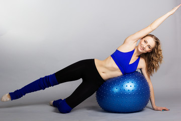 Young woman with blue fit-ball