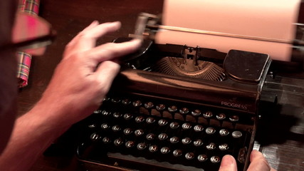 man typing on a typewriter