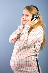 Beautiful pregnant blonde listens to music on headphones.