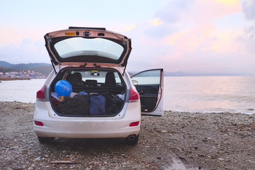 Car with open trunk on a sea coast