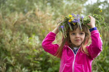 The smiling little girl in rose jacket on the nature with wreath