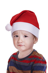Baby boy with a Santa cap looking sad and upset