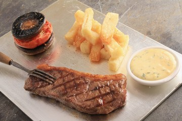 sirloin steak on silver platter with chips  tomato and mushroom