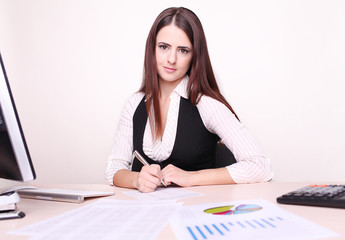 Portrait Of Happy Young Businesswoman Sitting At Desk Calculatin