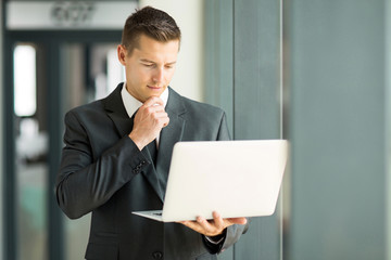 businessman reading email on his laptop