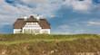 Leinwanddruck Bild - Reetdachhaus direkt am Meer im Sommer