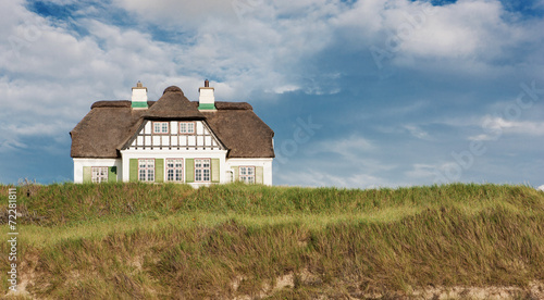 Leinwanddruck Bild Reetdachhaus direkt am Meer im Sommer