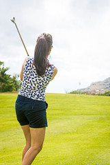 Female golfer hits approach shot from fairway to red flag on gre