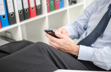 Relaxed businessman using his smartphone