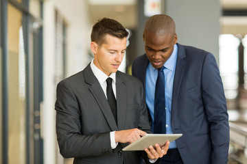 two businessmen using tablet computer