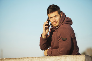 Young Sport Man With Hood Talking On Mobile Phone Outdoors