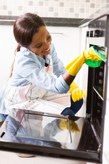 african woman cleaning oven