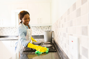 african woman cleaning the stove