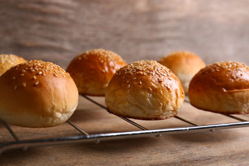 Tasty buns with sesame on oven-tray, on wooden background
