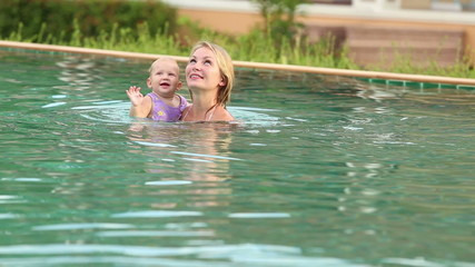 child and mother swim in the pool