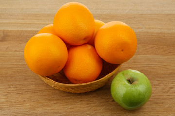 Juicy oranges and apple on wooden table, close-up
