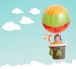canvas print picture - cute kid on hot air balloon in the blue sky