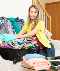 smiling woman packs suitcase