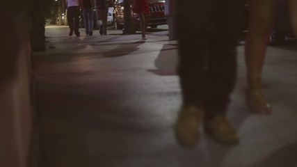 Evening shot of unrecognizable people walking on a sidewalk