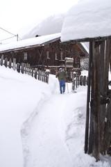Tief verschneiter Weg mit alten Häusern und Person