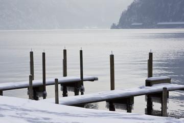 Verschneiter Steeg in den See mit Bergen im Hintergrund