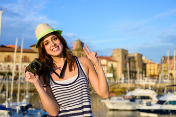 Successful happy tourist with camera by the harbor