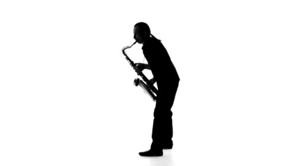 Silhouette of musician emotionally plays the saxophone on a