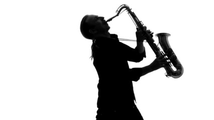 Close up of silhouette of musician playing the saxophone on a