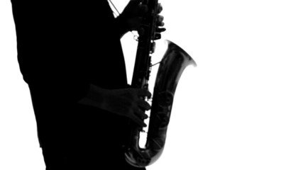 Dark silhouette of musician playing saxophone on a white