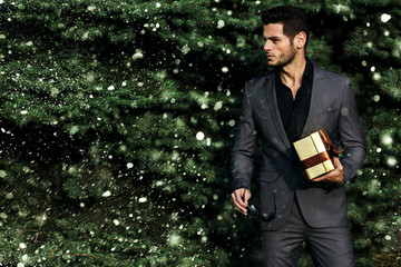 Man holding a gift near the Christmas tree