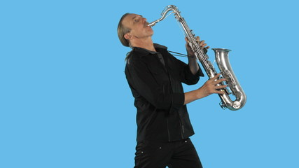 Professional saxophonist plays on his musical instrument in