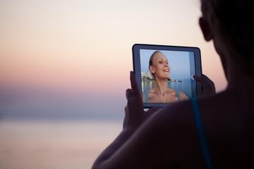 Woman making selfie on resort using pad